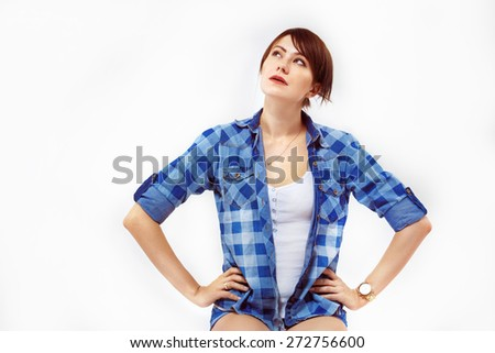A portrait of a young beautiful girl who is sitting akimbo and thinking new idea on isolated whited background. - stock photo