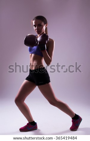 A portrait of a young beautiful girl with boxing gloves, isolated on grey background with poor light for Silhouette effect. - stock photo