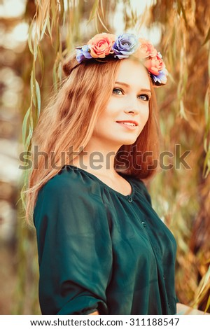 A portrait of a young beautiful russian lady in the nature of Tirana, Albania. A model looking up in the sky and kindly smiling, wearing a green blouse and flower crown.
