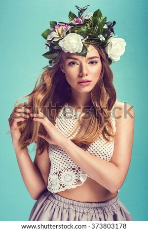 A portrait of a young beautiful woman with white flowers on the head. Spring fashion photo - stock photo