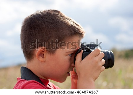 A portrait of a young boy, taking photos
