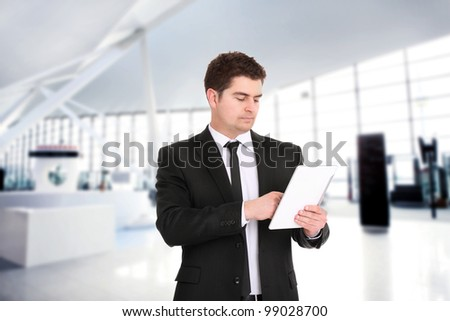 A portrait of a young businessman standing over the background of his modern office and using tablet computer