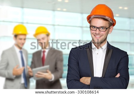 A portrait of a young businessman wear a safety helmet. team working at the back