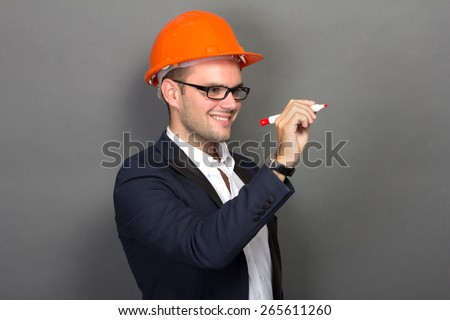 A portrait of a young businessman wear a safety helmet, writing - stock photo