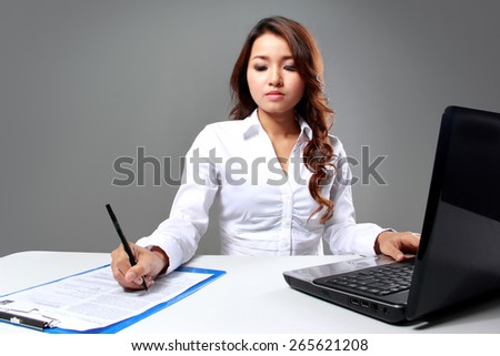 A portrait of a young businesswoman writing  while working with a laptop - stock photo