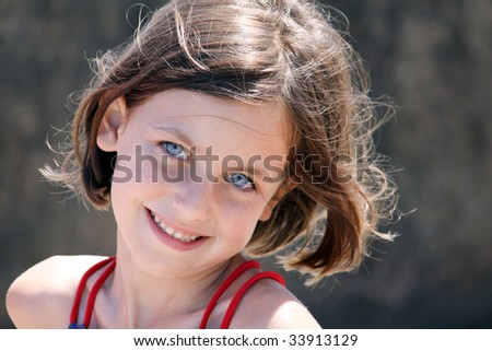 a portrait of a young caucasian child with blue eyes smiling at the camera
