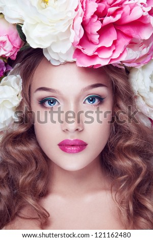 A portrait of a young girl with white and rosy peony on the head - stock photo