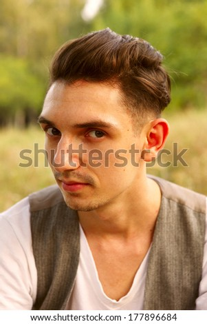 A portrait of a young handsome man posing outdoors. - stock photo