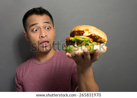 A portrait of a young man surprised with the size of his burger - stock photo