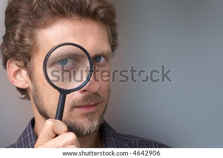 A portrait of a young man with a magnifying glass - stock photo