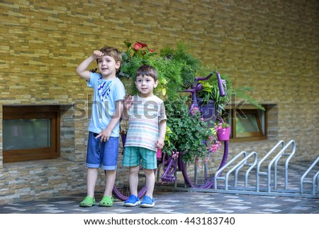 A portrait of a young smiling boys in striped shirt in park at evening. Boys interact with each other. brothers are smiling and discussing something. - stock photo