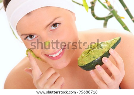 A portrait of a young woman applying natural avocado mask on her face - stock photo