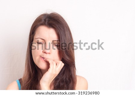 a portrait of a young woman biting her nails, horizontal image - stock photo