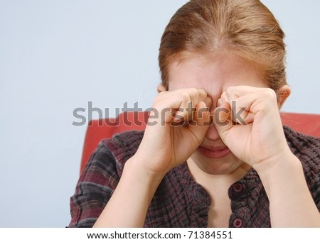 A Portrait of a Young Woman Crying with her Fists Raised to her Eyes with Room for Text