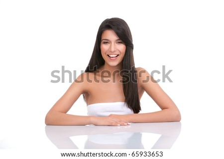 a portrait of a young woman, posing on a white background. she has her arms on a white table; she has a wide smile and a relaxed face expression. - stock photo