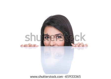 a portrait of a young woman, posing on a white background. she only has the tips of her fingers on a white table and only her eyes and nose are showing from behind the table. - stock photo