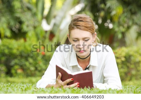 A portrait of a young woman reading a book in the park