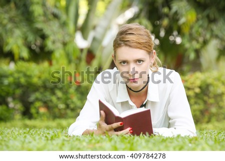 A portrait of a young woman reading a book in the park - stock photo