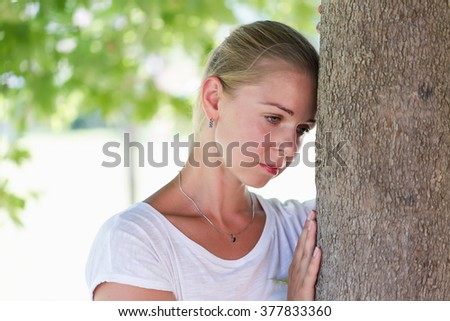A portrait of a young woman thiking in sadness in green summer background - stock photo