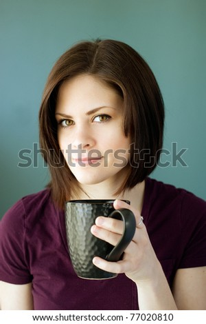 A portrait of a young woman with a black coffee mug. - stock photo