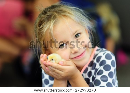 A portrait of an adorable little girl, preschool or school age, happy child holding a fluffy yellow baby chicken  with both hands and smiling  - stock photo