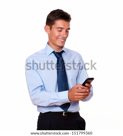 A portrait of an adult latin businessman texting and smiling while looking at his cellphone on isolated studio - stock photo