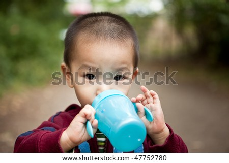 A portrait of an asian boy drinking from his cup - stock photo