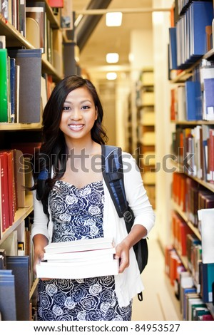 A portrait of an Asian college student in library - stock photo