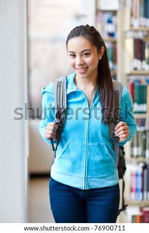 A portrait of an Asian college student studying in the library