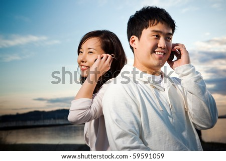 A portrait of an asian couple talking on the phone - stock photo