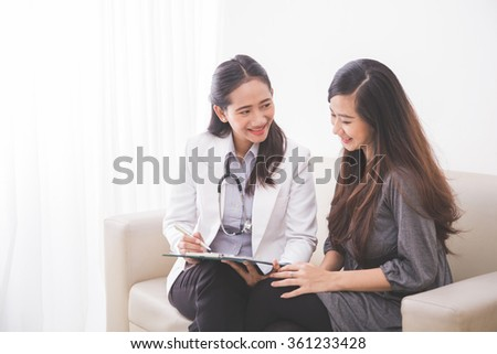 A portrait of an Asian female patient consulting with a female doctor - stock photo