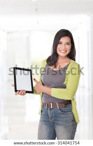 A portrait of an asian woman holding a digital touch screen tablet computer on white background. - stock photo