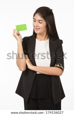A portrait of an Asian Woman in business formal black suit holding a green blank name card with her fingers. Isolated on white background. Close up half body.