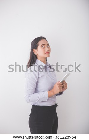 A portrait of an Asian Young secretary thinking while holding a smart phone. White background