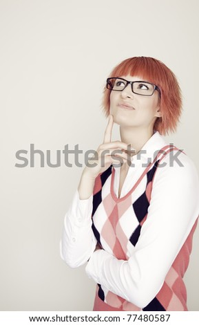 A portrait of an attractive girl with red hair and classes wearing a argyle vest - stock photo