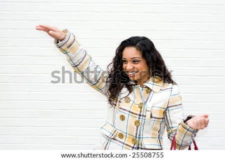 A portrait of an attractive young Indian woman waving to some friends or even hailing a taxi cab. - stock photo