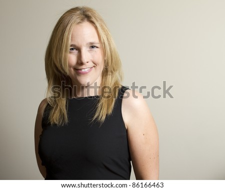 A portrait of an elegantly dressed young, attractive caucasian woman, smiling.