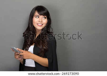 A portrait of Asian businesswoman with her phone looking up to copy space - stock photo