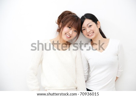 a portrait of beautiful asian sister isolated on white background - stock photo