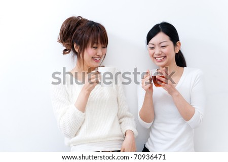 a portrait of beautiful asian sisters talking each other - stock photo