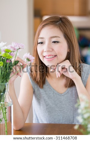 A portrait of beautiful asian woman with Mums flower - stock photo