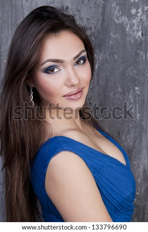 a portrait of beautiful brunette is in dark blue clothes - stock photo