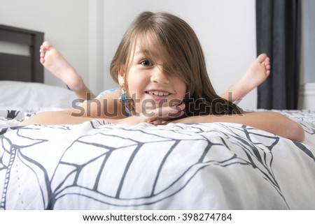 A Portrait of beautiful little girl lying on bed  - stock photo