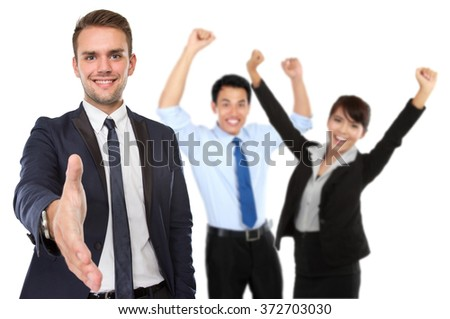 A portrait of businessman offering hand shake while happy team raise hand at the background - stock photo