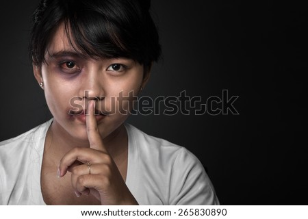 A portrait of close up of an asian girl. Holding her finger, showing to keep silent. - stock photo