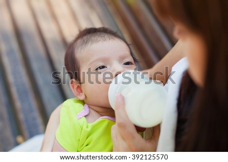 A portrait of cute newborn baby being fed by her mother using bottle - stock photo