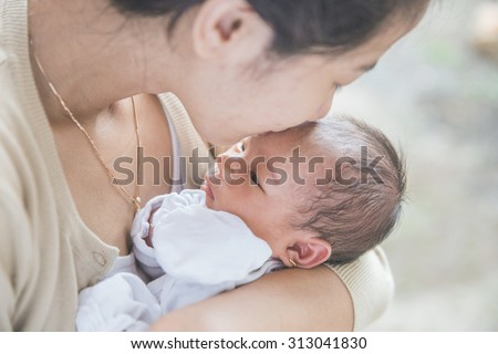 A portrait of cute newborn carried by her mother. kiss on her forehead - stock photo