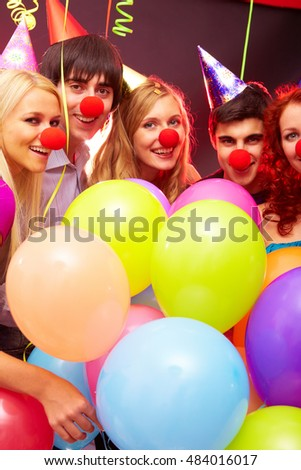 A portrait of five friends in party hats and clown noses among multicolored balloons, looking at camera and smiling