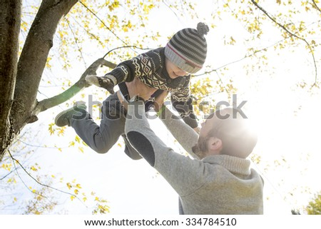 A Portrait of happy father with son in autumn park. - stock photo