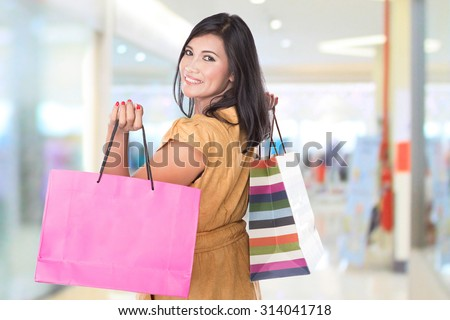 A portrait of happy middle aged Asian woman holding shopping bags